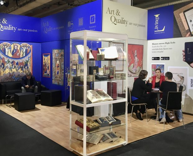 Frankfurter Buchmesse 2020 Exhibition booth FBM19 with glass showcase in front, on the right table with four chairs and one person sitting, left a black leather furniture