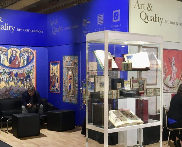 Frankfurter Buchmesse 2020 Messestand FBM19 mit Glasvitrine im Vordergrund, rechts hinten ein Tisch mit 4 Stühlen, davon drei besetzt und links eine freie Ledersitzgruppe.