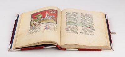 Aufgeschlagenes Buch der Faksimile-Auflage. Halbseitige Miniatur auf der linken Buchseite zeigt einen apokalyptischen Reiter auf schwarzem Pferd, der ein Schwert hoch hält und aus dem Höllenschlund springt. In der rechten oberen Ecke befindet sich ein Drache.
