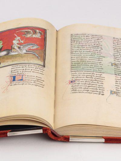 Aufgeschlagenes Buch der Faksimile-Ausgabe. Halbseitige Miniatur auf der linken Buchseite zeigt einen apokalyptischen Reiter auf schwarzem Pferd, der ein Schwert hoch hält und aus dem Höllenschlund springt. In der rechten oberen Ecke befindet sich ein Drache.